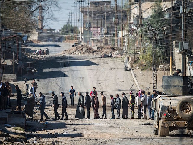 TOPSHOT - Men wait for their identity to be checked by soldiers from the Iraqi Special Forces' second division in Mosul's eastern district of Karkukli on November 18, 2016, during a massive operation to retake the last IS-held city in the country. The group of men was taken to a …