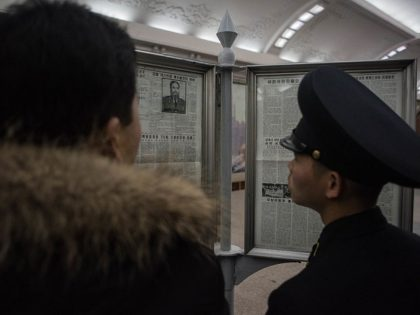 TOPSHOT - A guard reads a newspaper article announcing the death of former Cuban leader Fidel Castro, at a subway station in Pyongyang on November 28, 2016. / AFP / Ed JONES (Photo credit should read ED JONES/AFP/Getty Images)