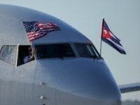 American Airlines plane fluttering US and Cuba national flags is seen uppon arrival at Jose Marti International Airport becoming the first Miami-Havana commercial flight in 50 years, coinciding with the beginning of the tributes to late Cuban leader Fidel Castro, on November 28, 2016 in Havana. / AFP / YAMIL LAGE (Photo credit should read