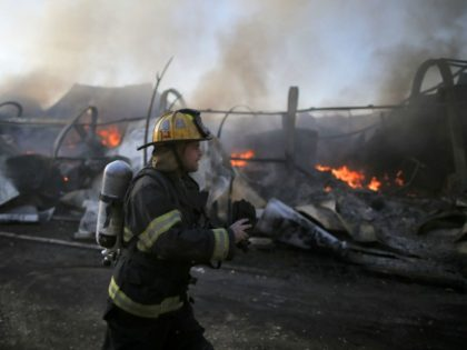 An Israeli firefighter inspects the damages in Beit Meir, a religious cooperative village in the hills to the west of Jerusalem, on November 25, 2016. Hundreds of people were evacuated during the night from November 24 to November 25 in the village of Beit Meir in central Israel, following the …