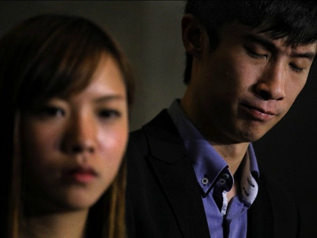 Newly elected Hong Kong lawmakers Yau Wai-ching, left, and Sixtus Leung react during a press conference outside the high court in Hong Kong Tuesday, Nov. 15, 2016. Two newly elected Hong Kong separatist lawmakers who used anti-China insults when being sworn in were disqualified from taking office in a court decision Tuesday. A Hong Kong High Court judge ruled that Sixtus Leung and Yau of the Youngspiration party violated a section of the semiautonomous Chinese city's constitution, the Basic Law, as well as laws covering oaths taken by officials. (AP Photo/Vincent Yu)