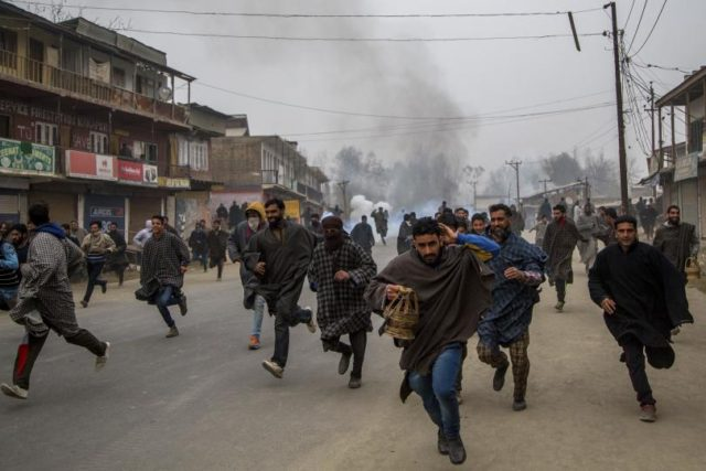 Kashmiri villagers run for cover from tear gas shells and pellets fired at them by Indian police during a protest near the funeral of Rayees Ahmad Dar, a suspected militant of Lashkar-e-Taiba (LeT) in Kakpora village south of Srinagar, Indian controlled Kashmir, Sunday, Nov. 20, 2016. Anti-India protesters attacked government …