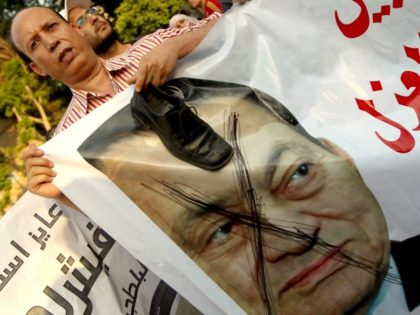 An Egyptian protester puts his shoe on a crossed portrait of Egypt's ousted president Hosni Mubarak during a protest in central Cairo on June 15, 2012 against the military-backed candidate Ahmad Shafiq, on the eve of Egypt's second round presidential election between Mubarak's last prime minister and his only rival, …
