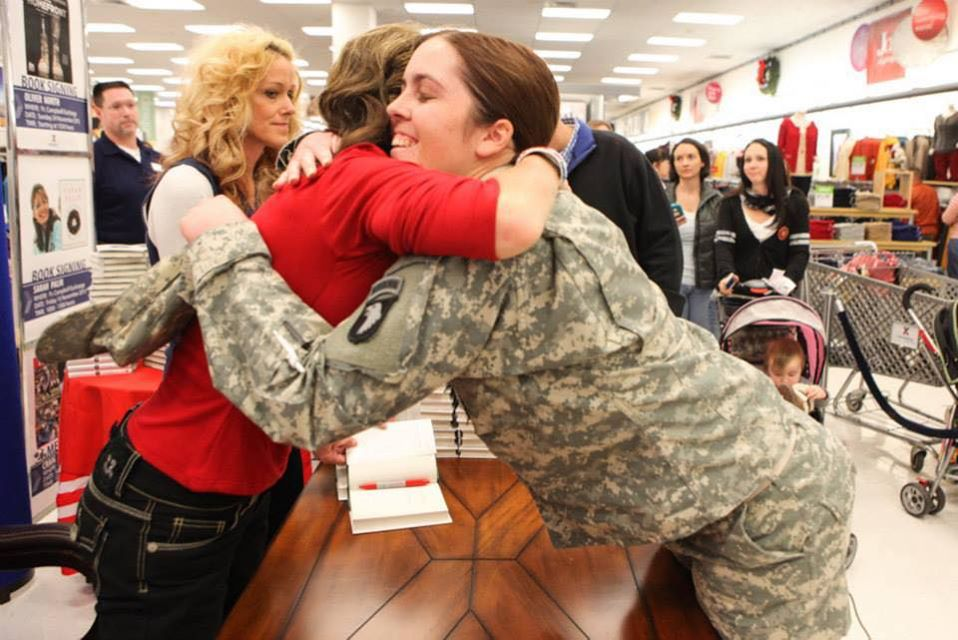 Palin embracing Bannon's daughter at a book signing at Fort Campbell, Kentucky in 2013.