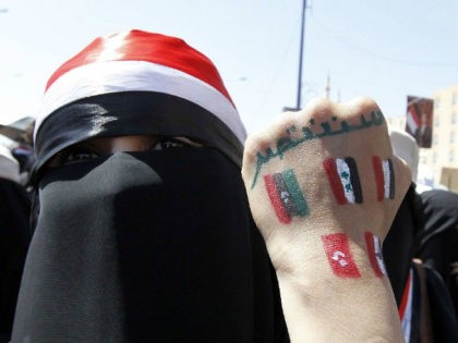 """(An anti-government protester displays paintings on her hand of other countries involved in the Arab Spring revolutions during a rally to demand the ouster of Yemen's President Ali Abdullah Saleh in Sanaa October 26, 2011. The words read, """"Go out."""" REUTERS/Louafi Larbi )"""
