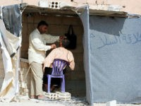 An Iraqi refugee who fled Mosul, the last major Iraqi city under the control of the Islamic State (IS) group, due to the Iraqi government forces offensive to retake the city, shaves the beard of a man at the UN-run Al-Hol refugee camp in Syria's Hasakeh province, on October 25, 2016. Despite the war that is ravaging Syria and has displaced millions of its residents, the Iraqis are desperate to reach the UN-run Al-Hol refugee camp in Syria's Hasakeh province, where many are still trapped on the border between Iraq and Syria under jihadist fire. / AFP / DELIL SOULEIMAN (Photo credit should read DELIL SOULEIMAN/AFP/Getty Images)