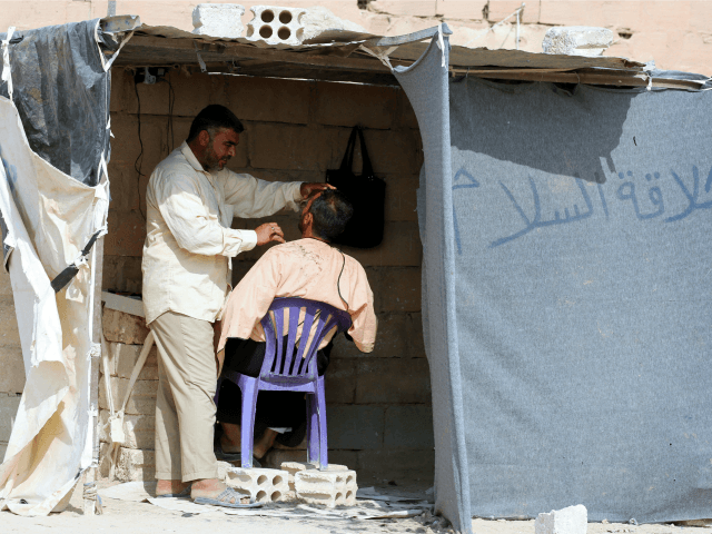 An Iraqi refugee who fled Mosul, the last major Iraqi city under the control of the Islamic State (IS) group, due to the Iraqi government forces offensive to retake the city, shaves the beard of a man at the UN-run Al-Hol refugee camp in Syria's Hasakeh province, on October 25, …