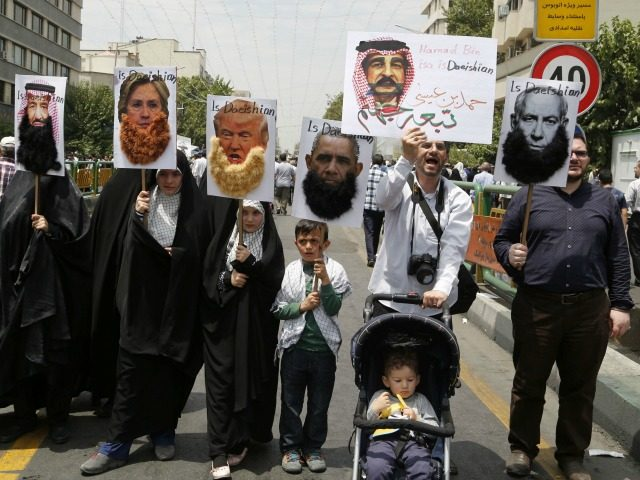 Iranian protesters hold portraits of (from L to R) Saudi King Salman, US Democrat presidential candidate Hillary Clinton, US Republican presidential candidate Donald Trump, US President Barack Obama, Bahraini King Hamad and Israeli Prime Minister Benjamin Netanyahu, most adorned with jihadist-style beards and a slogan reading 'is Daeishian' (Daesh is …