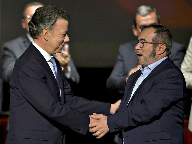 Colombian President Juan Manuel Santos (L) and FARC leader Timoleon Jimenez, aka Timochenko shake hands during the second signing of the peace agreement between the Colombian government and the FARC, at the Colon Theater in Bogota, Colombia, on November 24, 2016. Colombia's government and FARC rebels signed a controversial revised …