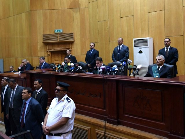 Egyptian police, lawyers and a judge (C-back) attend ousted Islamist president Mohamed Morsi's trial on espionage charges at a court in Cairo on June 18, 2016. An Egyptian court sentenced Morsi to life in prison in an espionage trial in which six co-defendants were handed death penalties.The court acquitted Morsi of charges of having supplied Qatar with classified documents but sentenced him to life for leading an unlawful organisation. / AFP / MOHAMED EL-SHAHED (Photo credit should read MOHAMED EL-SHAHED/AFP/Getty Images)