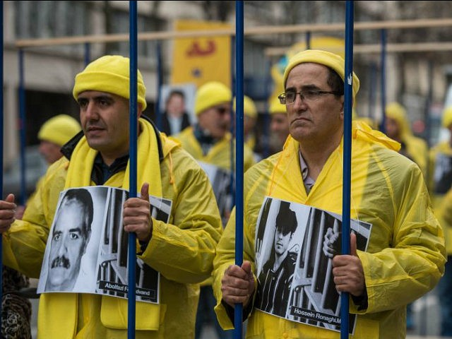 Demonstrators pose behind fake prison bars as Iranian opposition protesters march during a rally to protest against executions in Iran. Iranian President Hassan Rouhani is in France for a two-day official visit, in Paris, Thursday, Jan. 28, 2016. Rouhani's visit to Paris is focused on renewing trade ties, but France also wants to draw in Iran's help in peacemaking in the region, notably in Syria and Yemen, and easing tensions with regional rival Saudi Arabia. (AP Photo/Zacharie Scheurer)