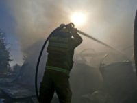 Israeli firefighters extinguish fire in Beit Meir, a religious cooperative village in the hills to the west of Jerusalem, on November 25, 2016. Hundreds of people were evacuated during the night from November 24 to November 25 in the village of Beit Meir in central Israel, following the spread of …