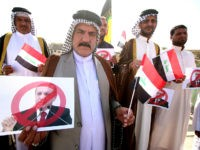 Iraqi tribesmen hold national flags and posters bearing a portrait of Turkish President Recep Tayyip Erdogan crossed out during a protest against the continued presence of Turkish troops in northern Iraq on October 16, 2016 outside the governorate building in the southern city of Basra. Turkish troops are deployed in …