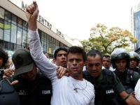 Opposition leader Leopoldo Lopez, dressed in white and holding up a flower stem, is taken into custody by Bolivarian National Guards, in Caracas, Venezuela, Tuesday, Feb 18, 2014. Lopez re-emerged from days of hiding to address an anti-government demonstration and then he turned himself in to authorities Tuesday. Speaking to …