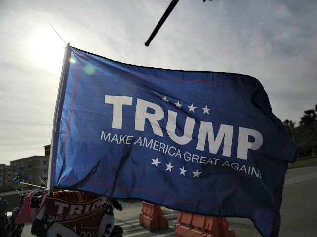"""A supporter shows a Donald Trump """"Make America Great Again,"""" flag before a campaign rally, Saturday, March 5, 2016, in Orlando, Fla. (AP Photo/Brynn Anderson)"""