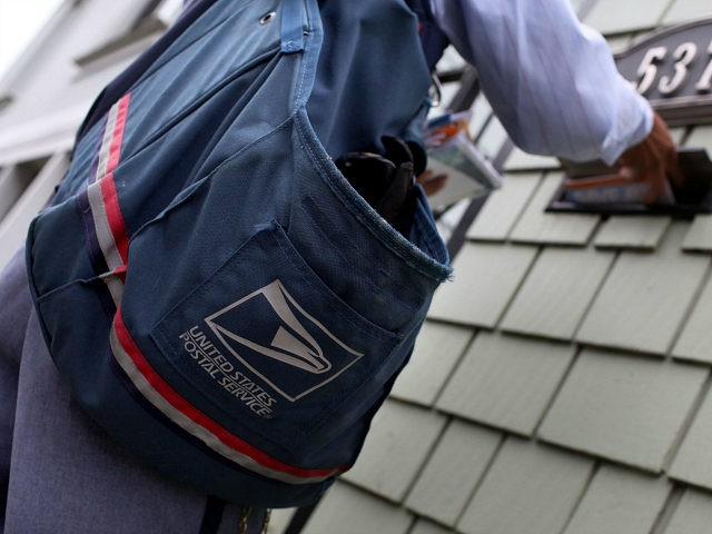 SAN FRANCISCO - JULY 30: US Postal Service letter carrier Anthony Ow places letters in a mailbox as he walks his delivery route July 30, 2009 in San Francisco, California. The US Postal Service is expecting their budget deficit to reach $7 billion, up from earlier projections of $6 billion. …