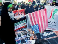 An Iranian youth burns home-made American flag outside the former US embassy in the Iranian capital Tehran on November 3, 2016, during a demonstration marking the anniversary of its storming by student protesters that triggered a hostage crisis in 1979. Thousands of Iranians took part in the demonstration, 37 years after the event that lasted for 444 days. / AFP / ATTA KENARE (Photo credit should read ATTA KENARE/AFP/Getty Images)
