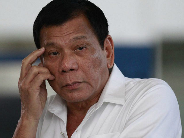 Philippine President Rodrigo Duterte listens to a question from reporters at Manila's International Airport, Philippines on Wednesday, Nov. 9, 2016. Duterte is set to fly to Bangkok to pay his respects to late Thailand's King Bhumibol Adulyadej. He then goes to Malaysia for an official visit. (AP Photo/Aaron Favila)