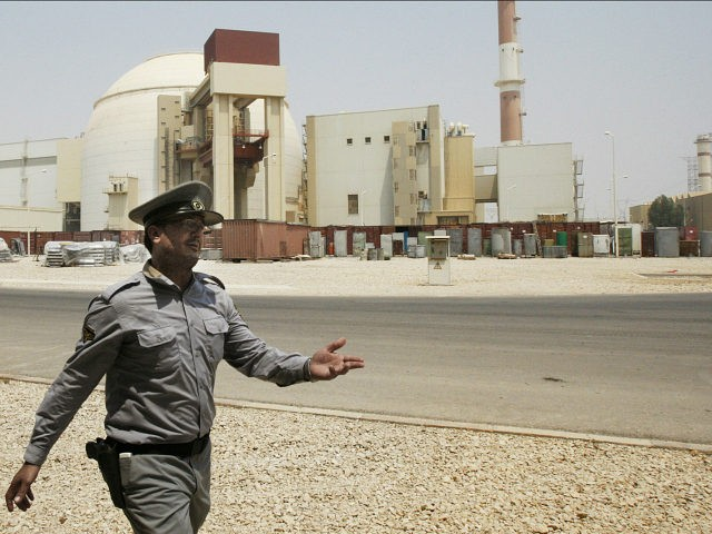 FILE - In this Aug. 21, 2010 file photo, an Iranian security officer directs media at the Bushehr nuclear power plant, with the reactor building seen in the background, just outside the southern city of Bushehr, Iran. State TV says the Guardian Council, Iran's constitutional watchdog, ratified a bill Wednesday, June 24, 2015, banning access to military sites and scientists as Tehran and world powers approach a deadline for reaching a comprehensive nuclear deal. The bill would allow for international inspections of Iranian nuclear sites within the framework of the Nuclear Non-proliferation Treaty. (AP Photo/Vahid Salemi, File)