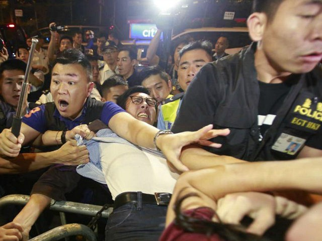 Protesters scuffle with police officers after clashing as thousands of people march in a Hong Kong street, Sunday, Nov. 6, 2016. Thousands of protesters marched in Hong Kong on Sunday, demanding that China's central government stay out of a political dispute in the southern Chinese city after Beijing indicated that it would intervene to deter pro-independence advocates. (AP Photo/Kin Cheung)