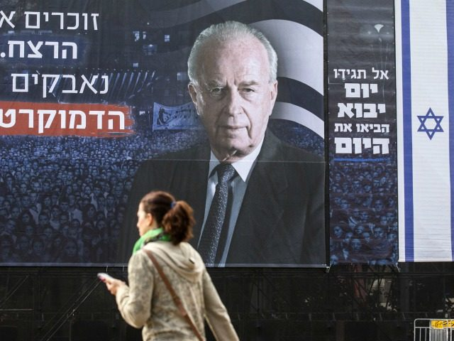 An Israeli woman walks past a billboard bearing a portrait of late Israeli prime minister Yitzhak Rabin, ahead of a memorial rally marking the 20th anniversary of Rabin's assassination, in the Israeli city of Tel Aviv, on October 29, 2015. Rabin, who led the way in the effort towards peace …
