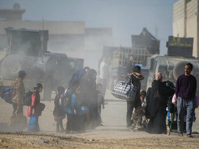People fleeing the fighting are seen walking to an area held by the Iraqi Special Forces 2nd division in the Samah neighbourhood of Mosul on November 17, 2016. Iraqi forces have broken into jihadist-held Mosul and recaptured neighbourhoods inside the city, but a month into their offensive, there are still …