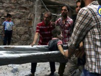 In this picture taken, Tuesday, Oct. 11, 2016, provided by the Syrian Civil Defense group known as the White Helmets, Syrian Civil Defense workers take out a boy, alive, from the rubble, in rebel-held eastern Aleppo, Syria. Activists and rescue workers say an intensive day of bombing on besieged rebel-held …