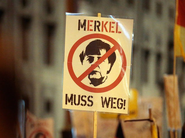 "MUNICH, GERMANY - JANUARY 11: Supporters of the right-wing populist group Pegida, holding a placard ""Merkel muss weg"" ('Merkel Off') march on January 11, 2016 in Munich, Germany. Pegida and other right-wing activists have been quick to latch on to the New Year's Eve sex attacks in Cologne. Over 100 …"