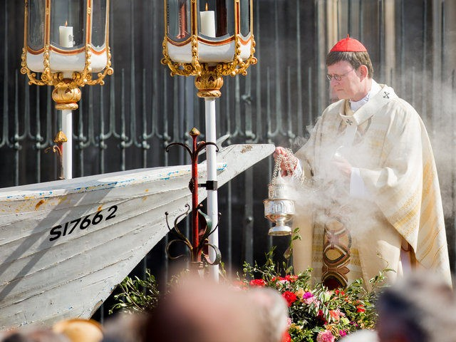 Cardinal and archishop Rainer Maria Woelki conducts the Corpus Christi Mass from a seven-meter-long refugee boat on May 26, 2016 in front of the cathedral in Cologne. Archbishop of Cologne, Cardinal Woelki celebrated the Corpus Christi Mass at the boat in memory of thousands of migrants who lost their lives …