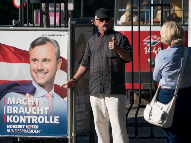 A man gives thumbs up in front of an election campaign poster of the presidential candidate Norbert Hofer from the far-right Freedom Party (FPOe) in Vienna, on August 31, 2016. Austria will re-run its presidential election on October 2. / AFP / JOE KLAMAR (Photo credit should read JOE KLAMAR/AFP/Getty …