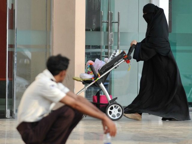 A Saudi woman walks past a foreign worker at the entrance of a shopping mall on November 7, 2013 in Riyadh. Saudis have begun complaining of surging labour costs following the exodus of a million foreign workers, although economists insist there will be long-term planning benefits from fully regulating the …
