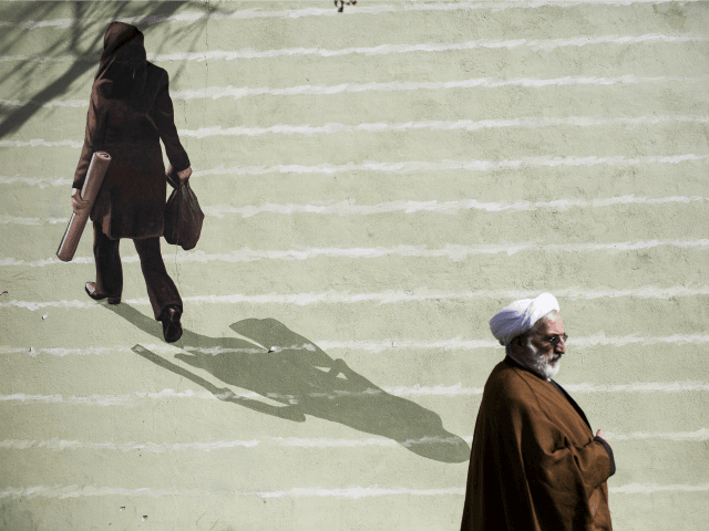 An Iranian cleric walks past a mural depicting a woman in downtown Tehran on February 24, 2016. / AFP / BEHROUZ MEHRI (Photo credit should read BEHROUZ MEHRI/AFP/Getty Images)
