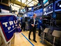 A trader walks past a campaign sign for U.S. President-elect Donald Trump and U.S. Vice President-elect Mike Pence on the floor of the New York Stock Exchange (NYSE) in New York, U.S., on Wednesday, Nov. 9, 2016. U.S. stocks fluctuated in volatile trading in the aftermath of Donald Trump's surprise …