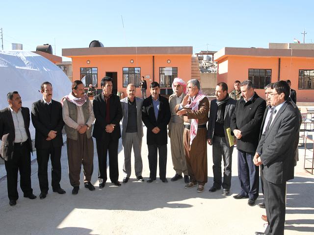 Sinjar Mayor Mahma Khalil Qasim near the middle with scarf around his neck.