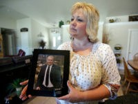 FILE - In this July 13, 2016 file photo, Laurie Holt holds a photograph of her son Joshua Holt at her home, in Riverton, Utah. At a press conference Tuesday, Oct. 11, 2016, attorney Jeanette Prieto said Holt was stripped naked and made to perform exercises in a hallway. She …