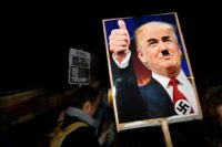 A demonstrator holds a placard showing a picture of US President-elect Donald Trump modified to add a swastika and an Adolf Hitler-style moustache during a protest outside the US Embassy in London