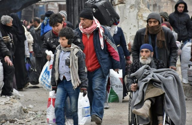 Syrian residents fleeing the eastern part of Aleppo gather in Masaken Hanano, a former rebel-held district which was retaken by the regime forces last week, on November 30, 2016
