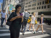 A pedestrian checks her smartphone while crossing a Fifth Avenue intersection in New York on Thursday, July 23, 2015. A bill introduced in New Jersey would make it illegal for anyone to text and walk at the same time. Offenders could be fined $50 and/or 15 days in jail. No …