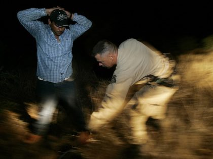 ** ADVANCE FOR WEEKEND EDITIONS, JULY 23-24 **A Border Patrol agent who asked not to be identified searches an illegal immigrant on the Tohono O'odham Nation in Arizona on June 9, 2005. The reservation is part of the Border Patrol's Tucson Sector__the busiest place in the country for illegal border …