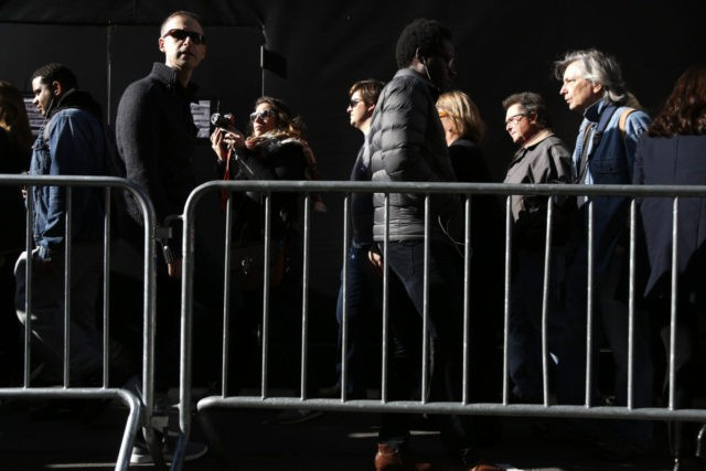 Pedestrians try to move through a slow moving crowd, behind police barricades, in front of Trump Tower in New York, Thursday, Nov. 17, 2016. (