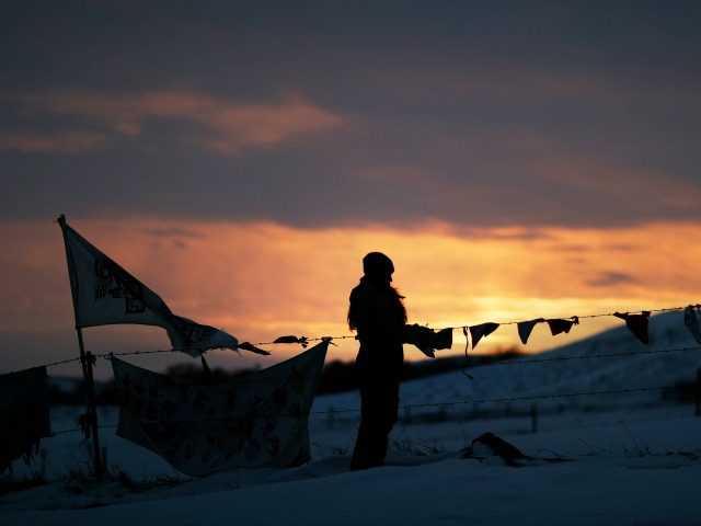 A woman watches the sunset at the Oceti Sakowin camp where people have gathered to protest the Dakota Access oil pipeline in Cannon Ball, N.D., Friday, Dec. 2, 2016. Hundreds of protesters fighting the Dakota Access pipeline have shrugged off the heavy snow, icy winds and frigid temperatures that have …
