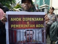 "A Muslim man holds a banner that reads ""Ahok in jail = fair government"" during a rally outside the North Jakarta court where Jakarta's Christian governor Basuki Tjahaja Purnama is on trial in Jakarta on December 13, 2016. Hardline Muslims rallied on December 13 under heavy police guard outside the …"