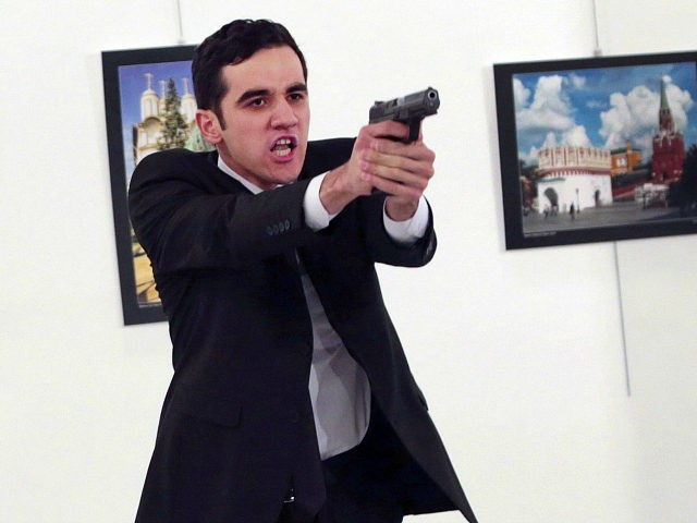 """ADDS THE NAME OF THE GUNMAN - A man identified as Mevlut Mert Altintas holds up a gun after shooting Andrei Karlov, the Russian Ambassador to Turkey, at a photo gallery in Ankara, Turkey, Monday, Dec. 19, 2016. Shouting """"Don't forget Aleppo! Don't forget Syria!"""" Altintas fatally shot Karlov in …"""