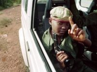 A child with a gun sits in a car on June 09, 1994 with Rwandan Patriotic Front (RPF) partisans patrolling the streets of Kigali, Rwanda. The UN headquarters came under attack as fierce fighting raged in the capital on June 09.        (Photo credit should read ABDELHAK SENNA/AFP/Getty Images)