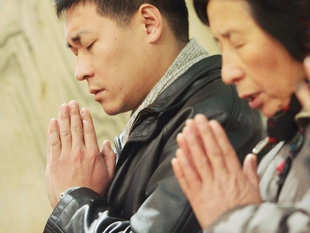 BEIJING, CHINA - DECEMBER 24: Catholics pray at Christmas Mass at a church on December 24, 2004 in Beijing, China. Though Christmas is not officially celebrated in China, the holiday is becoming increasingly popular as Chinese adopt more Western ideas and festivals. (Photo by Guang Niu/Getty Images)