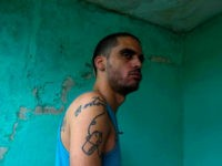 Danilo Maldonado, better known as El Sexto, stands at the entrance of his home after being released from jail, in Havana, Cuba, Tuesday, Oct. 20, 2015. Maldonado was freed after 10 months behind bars for attempting to release two pigs painted with the names of Raul and Fidel Castro, the country's current president and former leader. (AP Photo/Desmond Boylan)