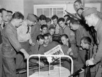 U.S. soldiers at the Presidio in San Francisco gather around the bed of one of their comrades, Dec. 7, 1941, to read an extra reporting of the bombing of Pearl Harbor, Hawaii, by the Japanese. (AP Photo/John Young)