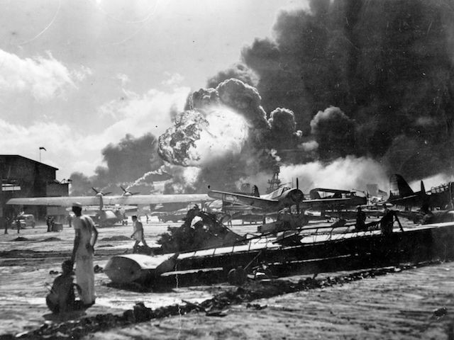 An explosion at the Naval Air Station, Ford Island, Pearl Harbour (Pearl Harbor) during the Japanese attack. Sailors stand amid wrecked watching as the USS Shaw explodes in the center background. The USS Nevada is also visible in the middle background, with her bow headed toward the left. (Photo by Fox Photos/Getty Images)