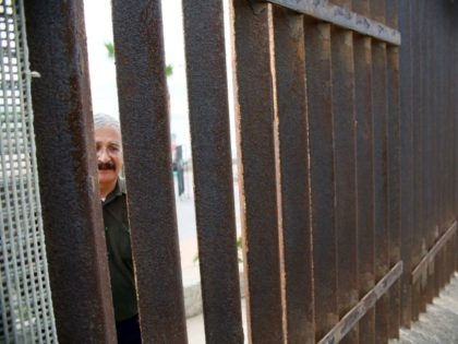 A Mexican National looks through the United States-Mexico Border wall in San Ysidro, California on Saturday, November 19, 2016. / AFP / Sandy Huffaker