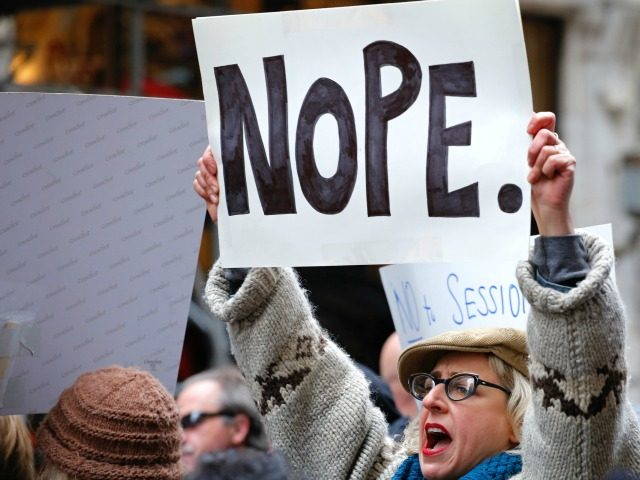 A woman protests against US President-elect Donald Trump in front of Trump Tower on November 20, 2016 in New York. / AFP / KENA BETANCUR (Photo credit should read